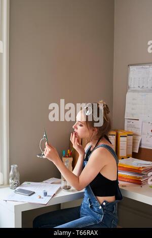 Mujer joven de aplicar el brillo de labios en el espejo Imagen De Stock