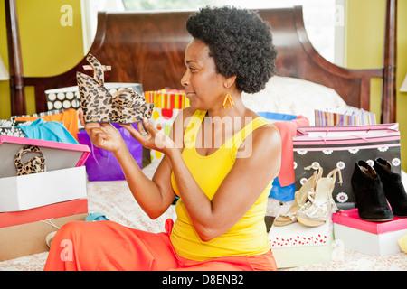 Mujer en la cama con los zapatos y bolsas de la compra. Imagen De Stock