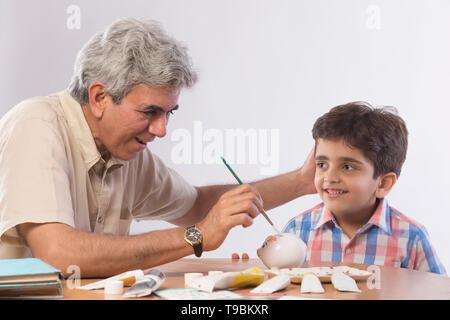 Abuelo y nieto de pintar hucha Imagen De Stock