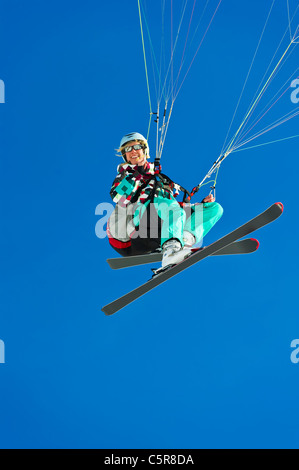 Una mujer piloto de parapente sonríe mientras volaba pasado. Imagen De Stock
