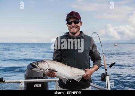 Retrato masculino confiado pescador capturando peces Imagen De Stock