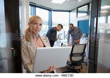 Retrato confianza empresaria con laptop en la sala puerta Imagen De Stock