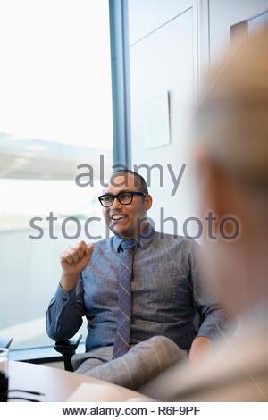 Empresario sonriente hablando en la sala reunión Imagen De Stock