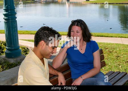 Pareja joven sentado en un banco de un parque hablando señor © Myrleen Pearson ...Cate Ferguson Imagen De Stock