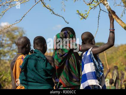Las mujeres de la tribu Suri viendo un donga ritual de combate con palo, valle de Omo Kibish, Etiopía Imagen De Stock