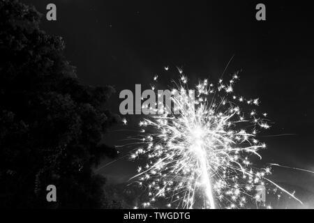 Fuegos artificiales iluminan el cielo de la noche en la víspera de Año Nuevo en Guatemala en blanco y negro impresionante Imagen De Stock