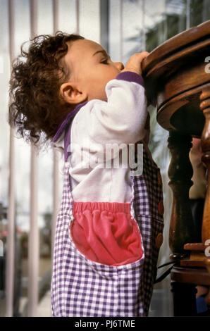 Niño tirando de ella hacia arriba para ver encima de la mesa. Señor © Myrleen Pearson ...Cate Ferguson Imagen De Stock