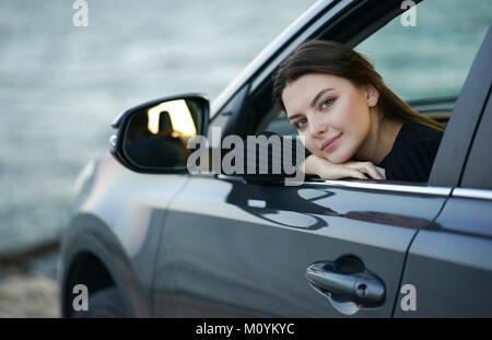 Sonriente mujer caucásica inclinándose en car window Imagen De Stock