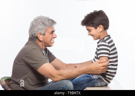 Abuelo y nieto de escuchar música con auriculares. Imagen De Stock