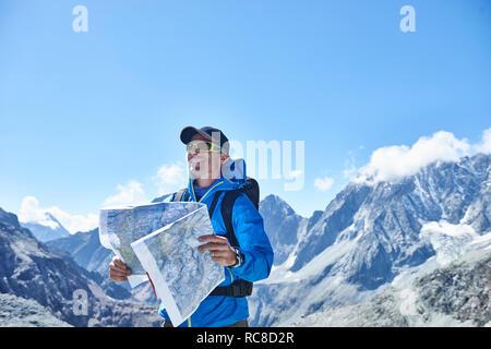 Hombre leyendo mapa, Mont Cervin, Cervino, Valais, Suiza Imagen De Stock
