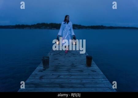 Una mujer con linterna sobre jetty Imagen De Stock