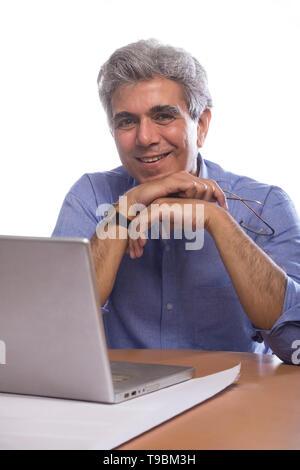 Retrato de altos hombre sentado en la mesa con el ordenador portátil Imagen De Stock