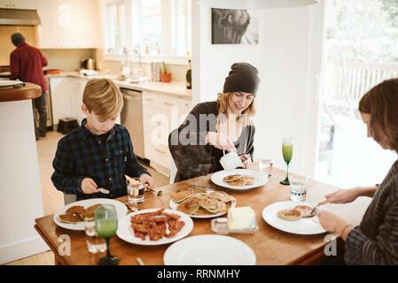 Familia desayunando en la mesa de la cocina Imagen De Stock