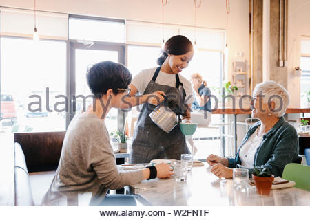 Camarera servir café para madre e hija en cafe Imagen De Stock