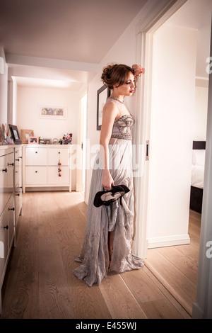 Cansado joven en vestido de noche, sosteniendo sus zapatos en el pasillo Imagen De Stock