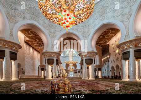 ABU DHABI, EMIRATOS ÁRABES UNIDOS - Noviembre 20, 2018: gran angular foto interior de la mezquita de Sheikh Zayed sala de oración. El primer plano muestra a una mujer v Imagen De Stock