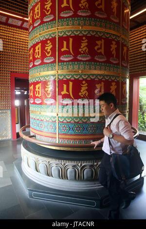 Adorador y Viarocana rueda de oración budista, la Reliquia del Diente de Buda Templo en Chinatown, Singapur, Sudeste de Asia, Asia Imagen De Stock