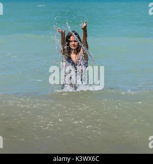 Una niña las salpicaduras de agua. Imagen De Stock