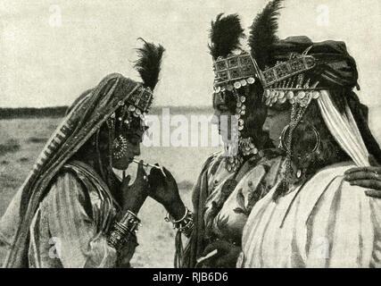 Tres mujeres de Argelia, Norte de África, en jewelled trajes, enciende un cigarrillo. Imagen De Stock