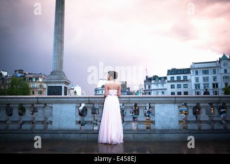 Mujer joven en vestido de noche al anochecer, Trafalgar Square, Londres, Reino Unido. Imagen De Stock