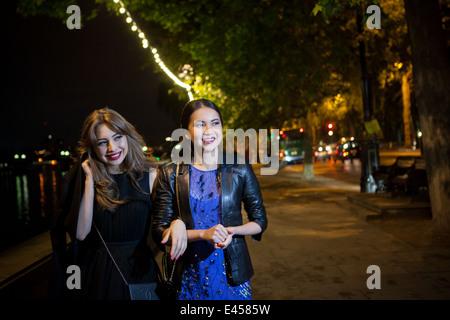 Dos amigas paseando a lo largo de Riverside en la noche Imagen De Stock