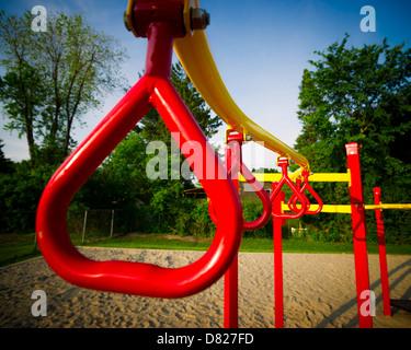 Composición de color rojo brillante y escalada barras oscilantes de una estructura de juegos infantiles al Imagen De Stock