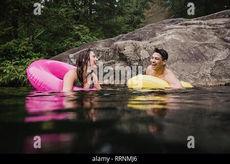 Feliz pareja joven flotando en los anillos inflables en el lago Imagen De Stock