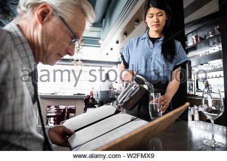 Camarera verter agua para altos hombre mirando el menú en un restaurante Imagen De Stock