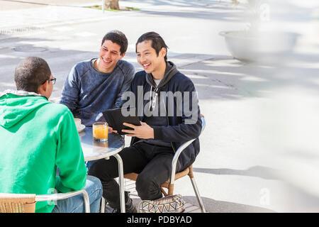 Amigos varones sonrientes hablando en la acera soleada cafetería Imagen De Stock