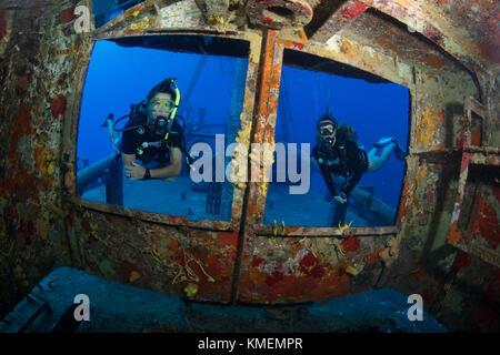 Los buceadores peer a través de windows en el puente de uss kittiwake Imagen De Stock