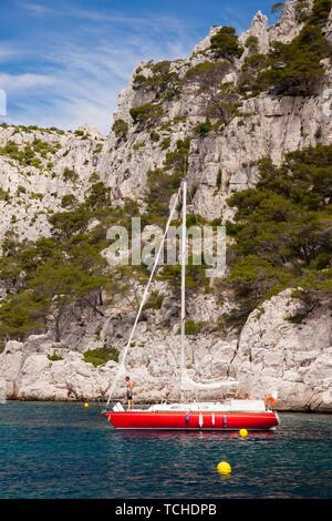 Velero rojo amarrado en uno de los Calanques cerca de Cassis, Provenza Francia Imagen De Stock