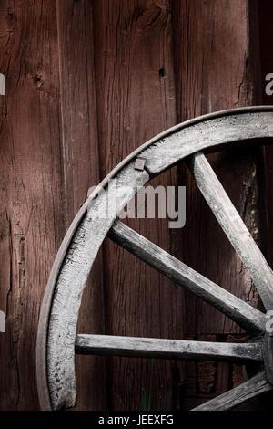 Rueda de carro antiguo fuera de las zonas rurales la pared del edificio. Nostalgia de madera rústica objeto. Imagen De Stock