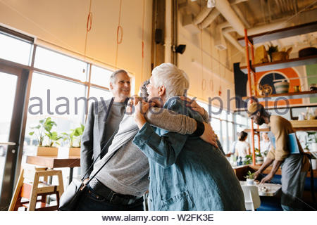 Saludo y abrazo feliz madre hija en cafe Imagen De Stock
