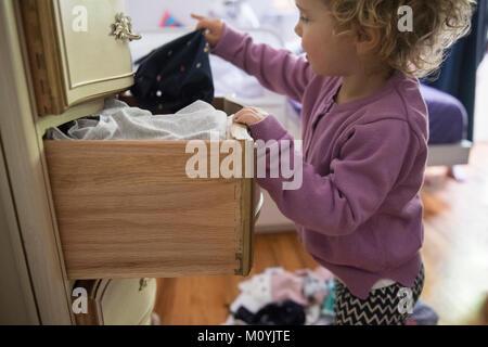 Chica caucásica retirando la ropa del cajón del aparador Imagen De Stock