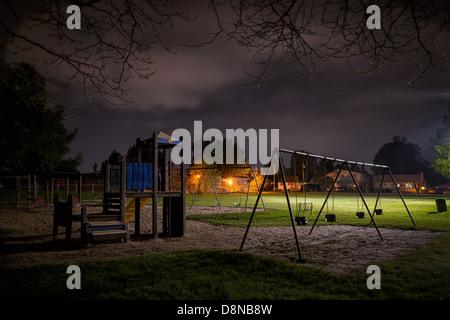 Una escalofriante escena de una desierta playground para niños en un parque suburbano durante la noche. Imagen De Stock