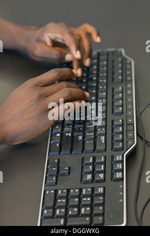 Cerca del afroamericano manos escribiendo en el teclado. Imagen De Stock