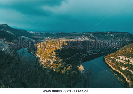 Vista panorámica de un río rodeado de montañas en el sol Imagen De Stock
