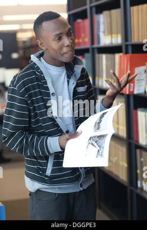 Estudiante universitario de 18 años de edad con una pregunta acerca de un libro, con gesto de mano. Imagen De Stock