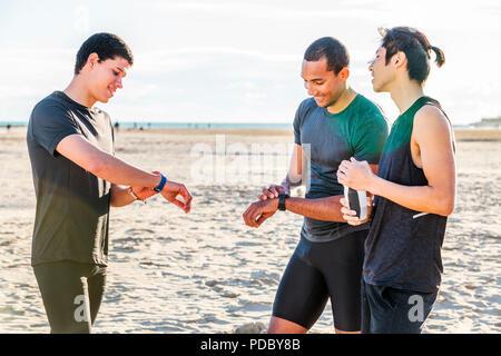 Los corredores masculinos control smart watch rastreadores de fitness en sunny beach Imagen De Stock