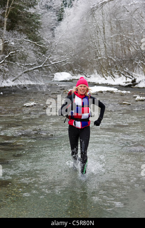 Un corredor ignora el agua fría y disfruta de un lecho de río nevado cruce. Imagen De Stock