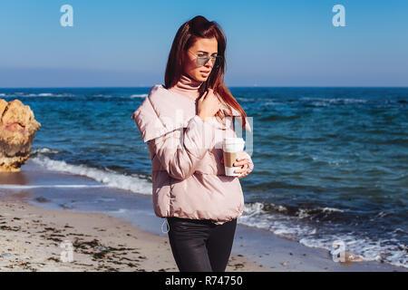 Elegante mujer adulta media paseando por la playa con café para llevar, Odessa, Odeska Oblast, Ucrania Imagen De Stock