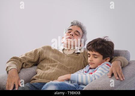 Abuelo y nieto durmiendo en el sofá Imagen De Stock