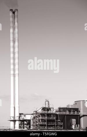 El fumar y el edificio industrial de la chimenea de una central eléctrica. Imagen De Stock