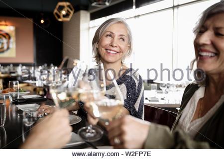 Feliz mujeres mayores amigos bebiendo vino en restaurante. Imagen De Stock