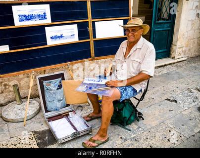 Artista sentado fuera de los muros de la ciudad vieja de Dubrovnik pintando con palos de bambú. Venta de obras de arte a los turistas. © Myrleen Pearson ...Cate Ferguson Imagen De Stock