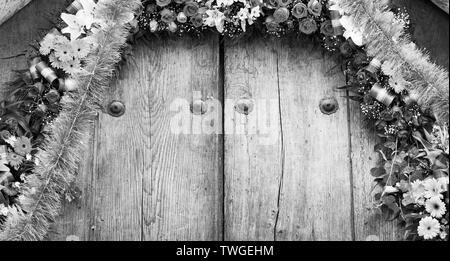 El arreglo floral en la antigua puerta de madera como fondo de textura en blanco y negro impresionante Imagen De Stock