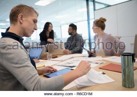 La empresaria revisando el papeleo en la sala reunión Imagen De Stock