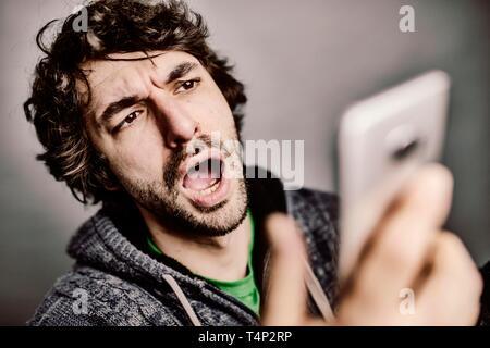Joven mira enojado, enfadado, sorprendido en su smartphone, Foto de estudio, Alemania Imagen De Stock