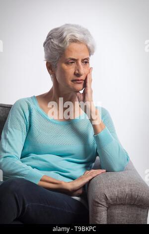 Retrato de mujer mayor pensando sentado en el sofá Imagen De Stock