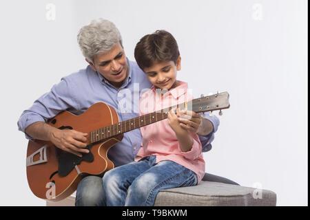 Abuelo y nieto tocando la guitarra Imagen De Stock
